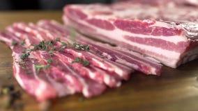 O cozinheiro polvilha o bacon cru pelo tomilho cutted, cozinhando a carne, refeições com os produtos de carne, cozinhando a carne video estoque