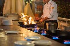 O cozinheiro prepara o alimento no calor elevado Prato quente imagem de stock royalty free