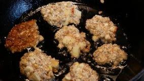 O cozinheiro prepara as costoletas em uma frigideira As panquecas pequenas são fritadas no óleo filme