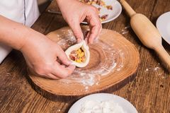 O cozinheiro prepara massa e carne semiacabadas imagem de stock