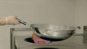 O cozinheiro prepara os vegetais em uma frigideira ardente vídeos de arquivo