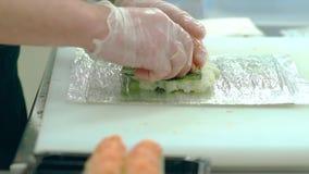 O cozinheiro prepara o sushi japonês com camarões, arroz e alga do nori Põe para fora os camarões vídeos de arquivo