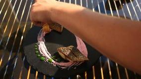 O cozinheiro principal decora um prato da culinária alta com a ajuda dos tenazes de brasa Close-up Peixes com batatas novas mulle filme