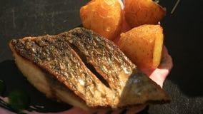 O cozinheiro principal decora um prato da culinária alta com a ajuda dos tenazes de brasa Close-up Peixes com batatas novas mulle video estoque