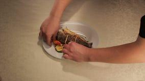 O cozinheiro Puts Fish na placa decora com vegetais video estoque