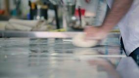 O cozinheiro que amassa a massa para o pão na tabela video estoque