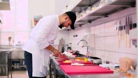 O cozinheiro que corta as polpas em umas partes pequenas video estoque