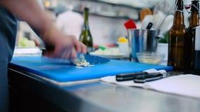 O cozinheiro que corta o alho na placa filme
