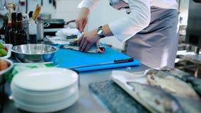 O cozinheiro que corta os peixes crus em duas partes na placa vídeos de arquivo