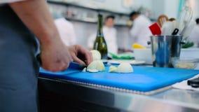 O cozinheiro que corta três cebolas na placa filme