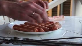 O cozinheiro remove a película protetora das salsichas filme