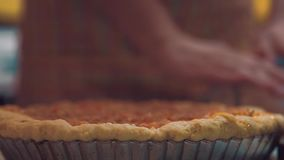O cozinheiro rola a massa atrás de uma base da torta filme