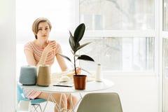 O craftswoman de Toughtful que relaxa com o vestido de confecção de malhas inteiro do copo de café com faz crochê no local de tra foto de stock