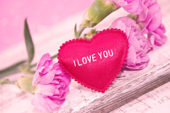 O cravo cor-de-rosa floresce com coração na tabela de madeira branca rústica Foto de Stock Royalty Free