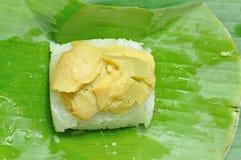 O creme cobriu o arroz pegajoso na licença da banana Fotos de Stock