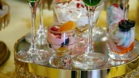 o creme e o souffle coloridos da sobremesa do fruto no projeto comemorativo do alimento do jantar do casamento de vidro deslizam  filme