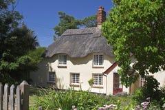O creme thatched a casa de campo no ajuste do jardim Foto de Stock Royalty Free
