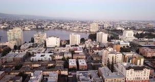 O crepúsculo cai nas construções e na skyline de Oakland, de CA e de lago Merritt vídeos de arquivo