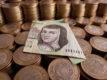 o crescimento econômico e a troca, empilharam moedas de dez pesos mexicanos e cédula de 200 pesos imagem de stock