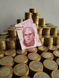 o crescimento econômico e a troca, empilharam moedas de dez pesos mexicanos e cédula de cinqüênta pesos foto de stock royalty free