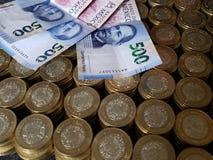o crescimento econômico e a troca, empilharam moedas de dez pesos mexicanos e cédulas de 500 pesos imagem de stock royalty free