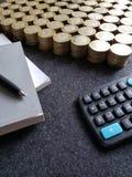 o crescimento econômico e a troca, empilharam moedas de dez pesos mexicanos, de livros, da pena preta e da calculadora imagens de stock