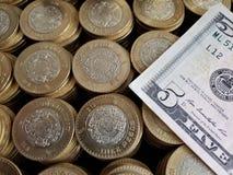 o crescimento econ?mico e a troca, empilharam moedas de dez pesos mexicanos e de americano cinco d?lares de conta foto de stock