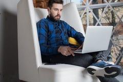 O criador à moda do homem situa a distância de funcionamento no laptop, assento no escritório moderno foto de stock royalty free