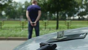 O criminoso detido nos grilhões está perto de um automóvel roubado vídeos de arquivo