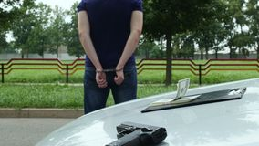 O criminoso detido nos grilhões está perto de um automóvel roubado video estoque