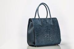 O crocodilo de couro azul gravou a bolsa das mulheres no backgroun branco Fotografia de Stock Royalty Free