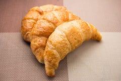 O croissant três partes arranjou em um pano marrom Fotos de Stock Royalty Free