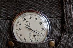 O cronômetro das antiguidades do vintage, em calças de brim marrons velhas pocket, medida do tempo do valor, minuto velho da seta Imagem de Stock