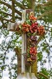 O crucifixo de pedra velho decorou com as flores no cemitério histórico Foto de Stock