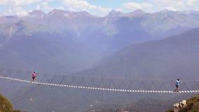 O cruzamento do abismo nas montanhas Os povos vão na ponte de corda através da falha Fotos de Stock Royalty Free