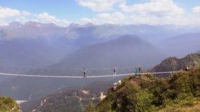 O cruzamento do abismo nas montanhas Os povos vão na ponte de corda através da falha Foto de Stock
