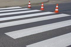O cruzamento pedestre cruz-decorado com o vermelho ainda não secado Limitação do tráfego por sinais de estrada Estrada da atualiz Fotos de Stock Royalty Free
