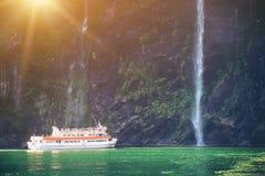 O cruzeiro c?nico aproxima a cachoeira, Milford Sound fotografia de stock