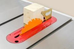 o cubo de madeira coloca em uma máquina circular da serra em um trabalho do woodworking fotografia de stock royalty free