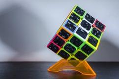 O cubo de Rubik na tabela escura imagem de stock