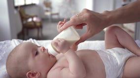 O cuidado da mãe, bebê no tecido está encontrando-se na tabela em mudança e no leite bebendo da garrafa que a mamã sustenta nela vídeos de arquivo
