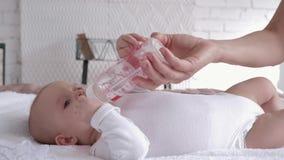 O cuidado da mãe, bebê recém-nascido está encontrando-se na cama e na água potável de uma garrafa que realizar do pai em suas mão filme