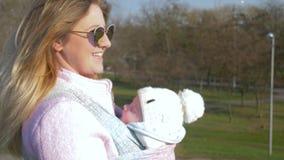 O cuidado do bebê, mãe bonita em vidros com criança anda fora no dia ensolarado filme
