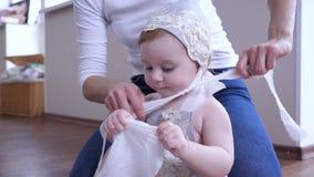O cuidado do bebê, mãe veste o beanie na cabeça da filha pequena em casa vídeos de arquivo