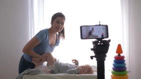 O cuidado do bebê, mamãe feliz do blogger muda a roupa do menino da criança ao gravar a vídeo de formação no celular para filme