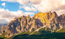 O cume rochoso da montanha de Pomagagnon acima do ` Ampezzo da cortina d com prados verdes e o céu azul com verão branco nubla-se imagem de stock