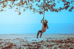 O curso asi?tico da mulher relaxa no feriado Sente-se em um balan?o na praia imagens de stock