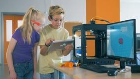 O curso da impressão 3D está obtendo controlou por duas crianças de um tablet pc vídeos de arquivo