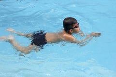 O curso de peito asiático do menino nada na piscina Fotos de Stock Royalty Free