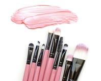 O curso e as escovas de creme bege da pintura da fundação cor-de-rosa da pele da cor compõem no fundo Fotografia de Stock
